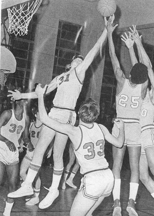 Black and White picture of a basketball player blocking a shot